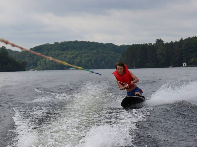 A camper kneeboarding at Arrowhead Camp.