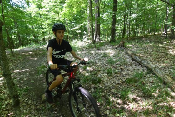 A camper goes mountain biking at Arrowhead Camp.