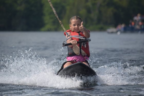 A camper is happy to be out kneeboarding at Arrowhead Camp.
