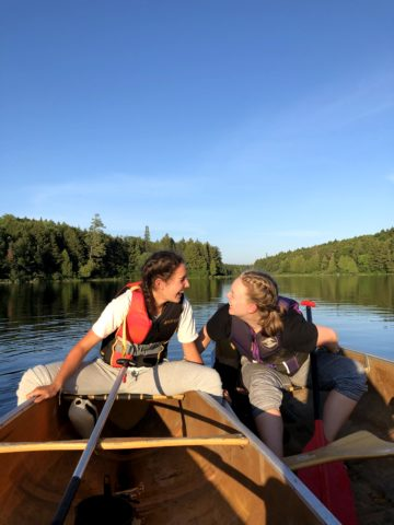 Campers on a canoe trip laughing after a long day of paddling in Algonquin Park.