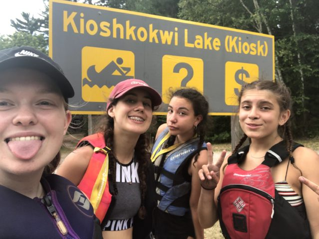 Campers posing by the Kiosk sign on their last day of an Algonquin Park canoe trip with Arrowhead Camp.